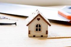 Modell des Hauses auf einem hölzernen Hintergrund Das Konzept des Baus und der Erneuerung Selektiver Fokus stockfotografie