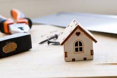 Modell des Hauses auf einem hölzernen Hintergrund Das Konzept des Baus und der Erneuerung Selektiver Fokus stockfoto