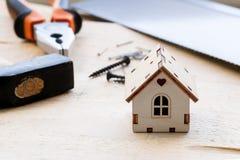 Modell des Hauses auf einem hölzernen Hintergrund Das Konzept des Baus und der Erneuerung Selektiver Fokus lizenzfreies stockfoto