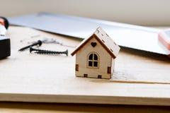 Modell des Hauses auf einem hölzernen Hintergrund Das Konzept des Baus und der Erneuerung Selektiver Fokus lizenzfreie stockbilder
