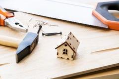 Modell des Hauses auf einem hölzernen Hintergrund Das Konzept des Baus und der Erneuerung Selektiver Fokus lizenzfreies stockbild