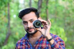 Modell des jungen Mannes, das ein Kameraobjektiv vor seinem Gesicht mit Fokus hält lizenzfreies stockbild