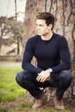 Modell des jungen Mannes in einem Park unter einem Baum Lizenzfreies Stockfoto