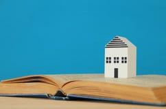 Modell des kleinen Hauses über offenem Buch Selektiver Fokus Stockfotografie