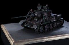 Modell des russischen Kampffahrzeugs des Behälters T-34, mit drei Soldaten in der Nähe Schwarzer Hintergrund stockfoto