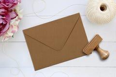 Modell des Umschlags mit einem Stempel nahe bei ihm Lizenzfreie Stockbilder