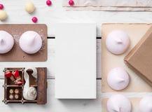 Modell des weißen Kastens zwischen Bonbons auf dem Tisch Stockfoto