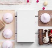 Modell des weißen Kastens zwischen Bonbons auf dem Tisch Lizenzfreie Stockbilder