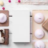 Modell des weißen Kastens zwischen Bonbons auf dem Tisch Stockbilder