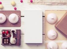 Modell des weißen Kastens zwischen Bonbons auf dem Tisch Lizenzfreie Stockfotos