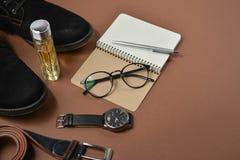 Modell för faderdag med pennan, doft, bältet, skodon, notepaden och glasögon på brun bakgrund Ställ in av stilfull manlig kläder  arkivbilder