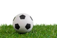 Modell för fotbollboll på konstgjort grönt gräs med vit backgroun Arkivbild
