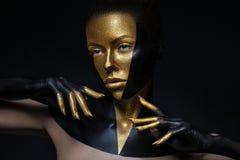 Modell för högt mode med svart och guld- läder, guld- fingrar Isolerat på kvinnlig framsida för svart bakgrundsskönhet, idérikt s royaltyfri foto