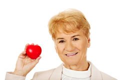 Modell för hjärta för äldre kvinna för leende hållande Arkivbild