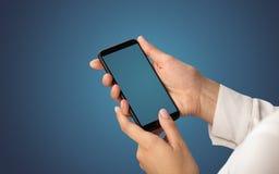 Modell för kvinnlig hand genom att använda smartphonen royaltyfri bild