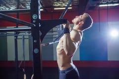 Modell för muskulös kondition för idrottsman nen som manlig drar upp på horisontalstång i en idrottshall Crossfit stil Royaltyfria Bilder