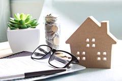 Modell för Wood hus, mynt, glasögon och besparingkontobok eller bokföringsunderlag på tabellen för kontorsskrivbord royaltyfri bild