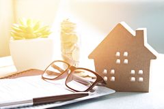 Modell för Wood hus, mynt och bokföringsunderlag eller besparingkontobok på skrivbordtabellen Royaltyfri Bild