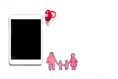 Modell für Annahmekonzept PC nahe Babyfriedensstifter, Papierschattenbild der Familie auf weißem copyspace Draufsicht des Hinterg stockbilder