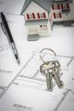 Modell Home, blyertspenna och tangenter som vilar på husplan Royaltyfria Bilder