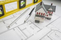 Modell Home, nivå, blyertspenna och linjal som vilar på husplan arkivfoto