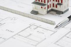 Modell Home, tekniker Pencil och linjal som vilar på husplan Arkivbilder