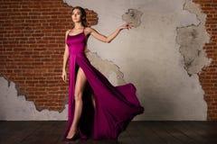 Modell i den eleganta klänningen, kvinna som poserar i den siden- torkduken för flyg som vinkar på vind, skönhetmodestående arkivbilder