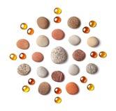 Modell i form av en cirkel av kulöra kiselstenar och orange glass pärlor som isoleras på vit bakgrund fotografering för bildbyråer