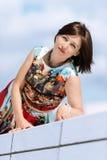 Modell i klänningen som poserar på yttersidauppsättninglodlinje Royaltyfri Bild
