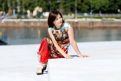 Modell i klänningen som poserar på yttersidauppsättningsammanträde Arkivfoto
