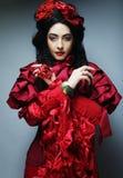Modell i röd dräkt för elegans Royaltyfria Foton