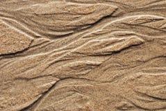 Modell i tidvattens- sand Arkivbild
