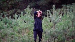 Modell kleidete in den schwarzen Roben an, die einen grünen Park zeigen stock video
