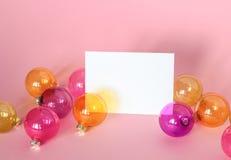 Modell med inbjudankortet på ljus - rosa bakgrund med julprydnader arkivbild