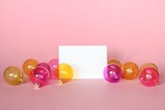 Modell med inbjudankortet på ljus - rosa bakgrund med julprydnader Royaltyfri Foto