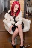 Modell med livligt rött hår i stol Arkivbild