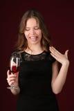 Modell mit dem Wein, der Zunge zeigt Abschluss oben Dunkelroter Hintergrund Stockfotografie