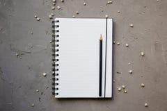Modell mit sauberem Notizblock und kleinen weißen Blumen, Draufsicht Flache Lage des leeren Notizbuches und des Bleistifts, Kopie stockfoto