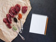 Modell mit Steak des Rindfleisches auf Papier und Gewürzen lizenzfreie stockfotos