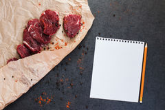 Modell mit Steak des Rindfleisches auf Papier und Gewürzen stockfotografie