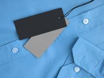 Modell mit zwei Aufkleber-Preisen auf blauem Hemd Lizenzfreie Stockfotos
