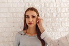 Modell- och makeupkonstnären gör en ny form naturliga ögonbryn Arkivbild