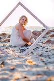 Modell på stranden till och med ram royaltyfria bilder