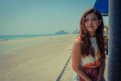 Modell saß auf der Wand, die hinunter Strand Hua Hin mit Tempelberg im Hintergrund betrachtet Lizenzfreie Stockfotos