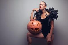 Modell som poserar med halloween pumpa Arkivbild
