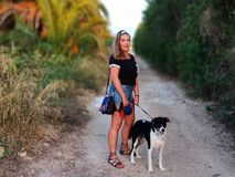 Modell som poserar på en väg med hennes husdjurvän arkivbilder
