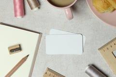 Modellaff?rskortet p? granit med anm?rkningsboken, gr?a och rosa tr?dar, kopp kaffe och kaka, tr?blyertspenna, v?ssare, linjal royaltyfri fotografi