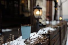 Modellannons: ett tomt anseende för pappers- kopp på ett staket i en gammal stadbakgrund royaltyfri fotografi