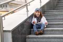 Modellbarnhöft-flygtur sammanträde på utomhus- trappa Royaltyfri Foto