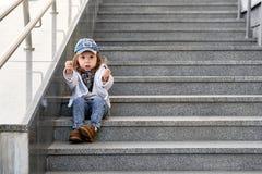 Modellbarnhöft-flygtur sammanträde på utomhus- trappa kläder för jeans för mode för flickabarngata fotografering för bildbyråer